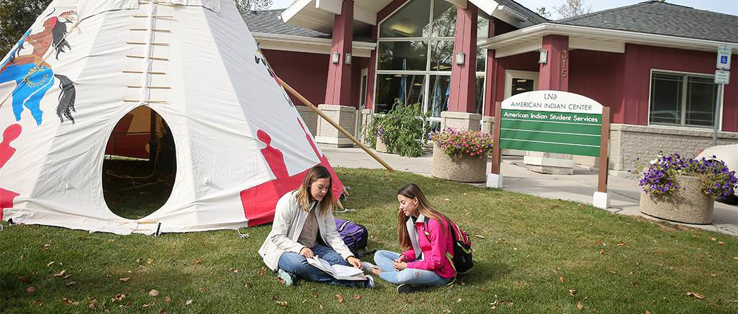 Students studying outside the AISS building on lawn