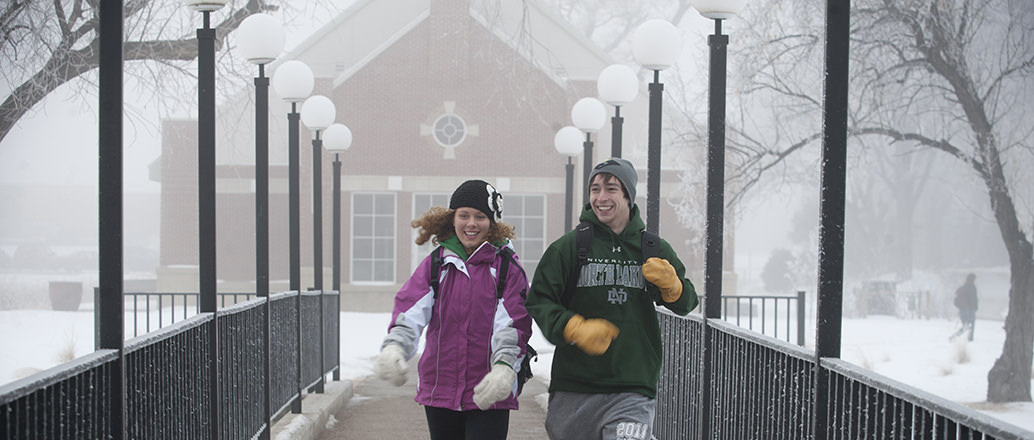 Students walking across a bridge in winter