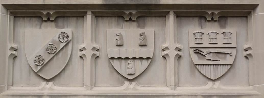 Three shields carved in the side of  a building