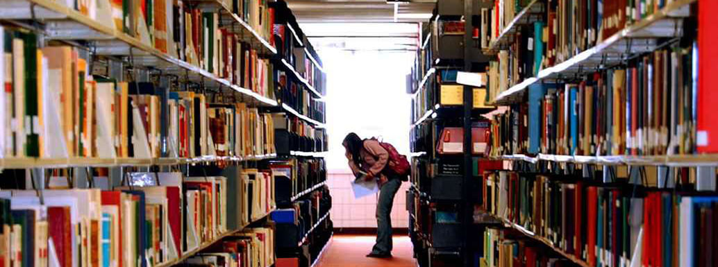 Student in UND library among stacks of books