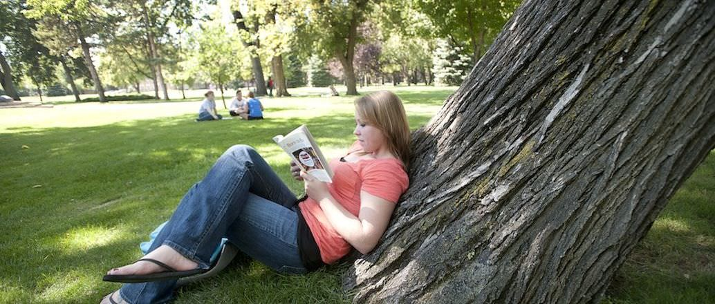 psychology student studying by tree