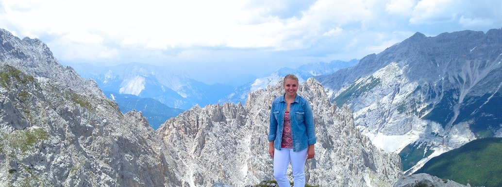 student studying abroad standing on mountain top