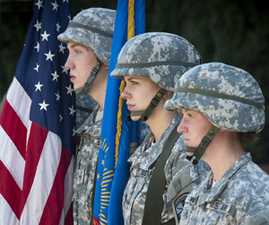 military members stand next to an American flag